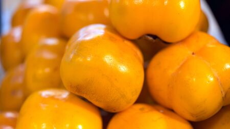Macro photo Asian fruit persimmon. Stock photo fresh fruit persimmons, Fresh ripe persimmons in market. Persimmons background.