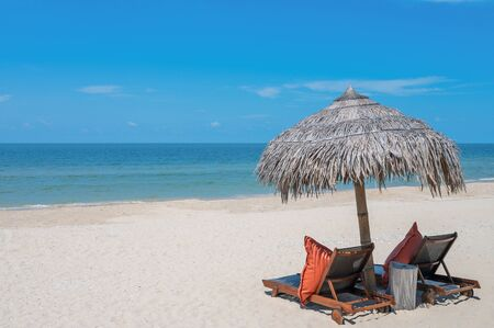 Two Chairs Under Parasol In Tropical Beach. turquoise sea, deckchairs, white sand and Kayak, sun, very beautiful nature