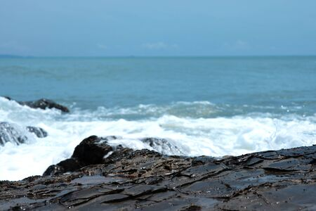 Wave crashing on the rocky reef. the waves of the ocean are breaking against the rocks. splashing ocean waves at sunset.