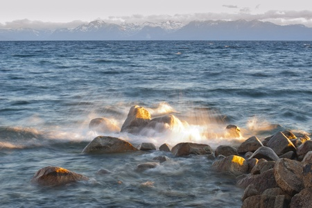 tahoe: Water splash on rock with mountain in the background at Lake Tahoe, California, USA