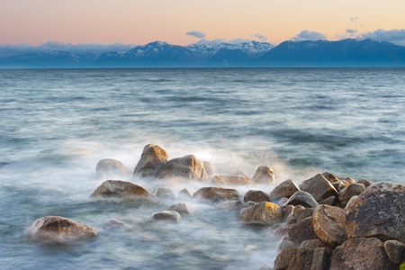 Water splash on rock with mountain in the background at Lake Tahoe, California, USA photo