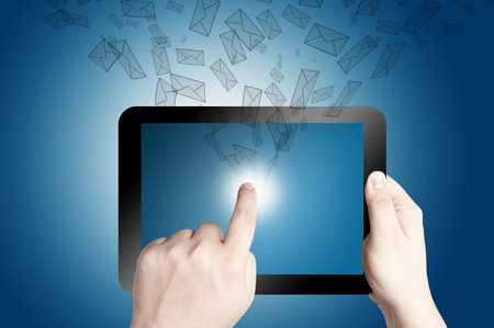 Hand holding and pointing on touch screen digital tablet with 3D mail icon coming from the screen on blue background photo