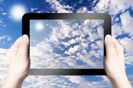 Hands holding on digital tablet with Cloudy sky background photo