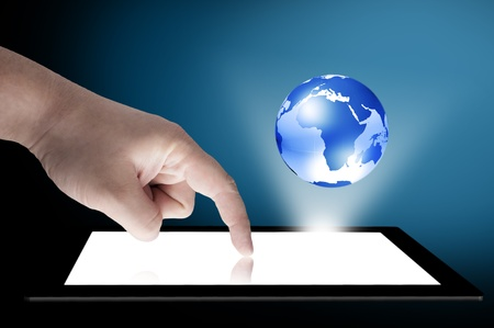 Businessman touch tablet PC screen with blue internet globe coming out from the screen  Concept for internet and connectivity Stock Photo - 13000559
