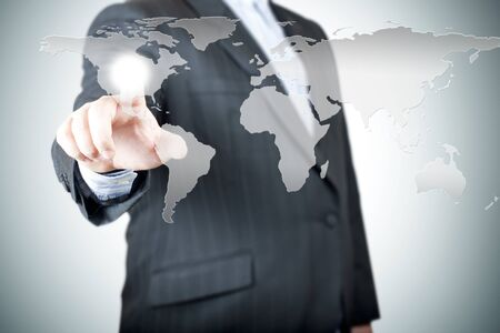 Business man pointing on the touch screen with world map  Concept for connectivity photo