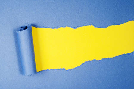 Torn blue color paper on yellow color background with space for text  photo