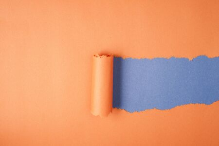Orange Tear Paper on blue background photo