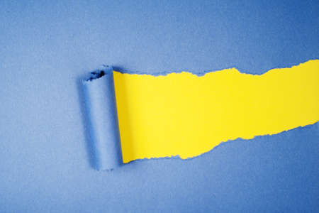 Blue Tear Paper on yellow background photo