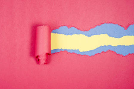 Red Tear Paper on yellow and blue background photo