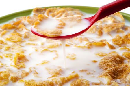 corn flakes: Close up on red spoon dipping into corn flakes Stock Photo