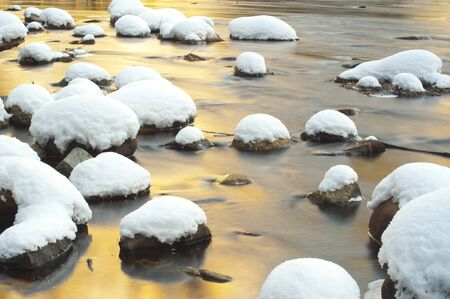 Snow on stone with water flow photo