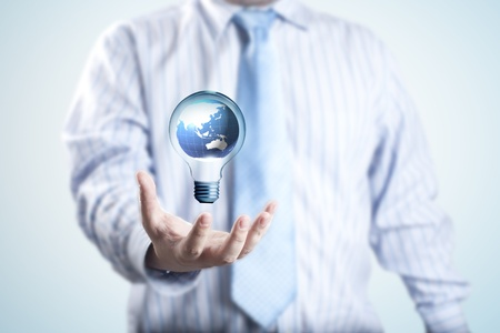 Business man with the digital globe inside light bulb floating on his hand  Concept for idea of connectivity within grasp  photo