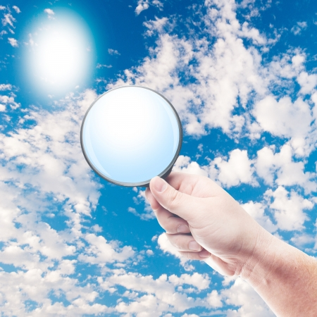 Hand Holding Magnifying Glass on blue sky photo