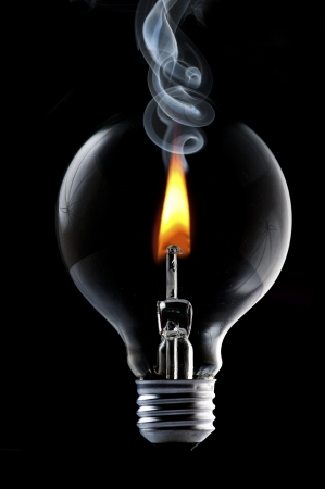 uncontrolled: Fire and smoke in side the light bulb  Concept for energy consumption and environmental awareness  Stock Photo
