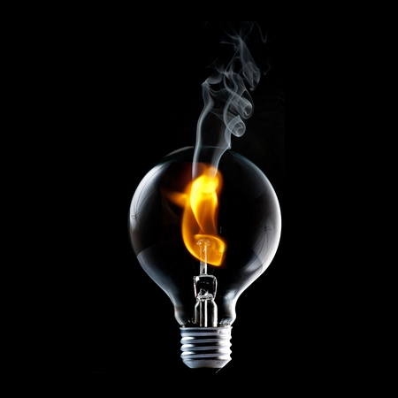 Fire and smoke in side the light bulb  Concept for energy consumption and environmental awareness  photo