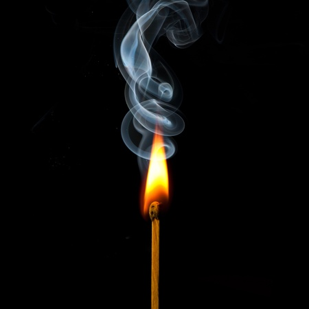 Spark of match with fire and smoke on black background photo