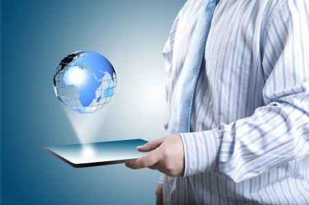 Businessman touch tablet PC screen with blue internet globe coming out from the screen  Concept for internet and connectivity Stock Photo - 14257199