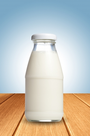 Milk on wooden floor and blue background photo