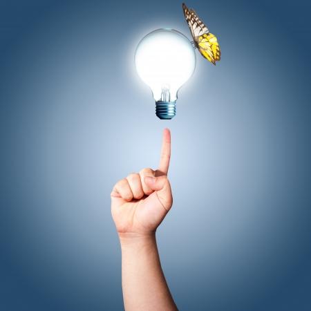 환경 친화적 인 나비 개념을 빛나는 전구에 손을 가리 스톡 사진