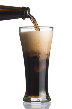 Dark beer pouring from bottle to glass isolated on white photo