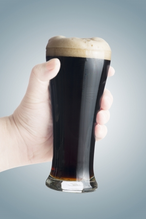 Hand holding fresh cold glass of dark beer photo