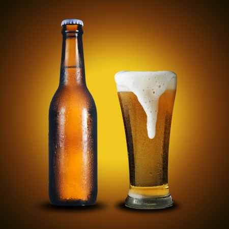 Fresh cold bottle and glass of beer on yellow background photo