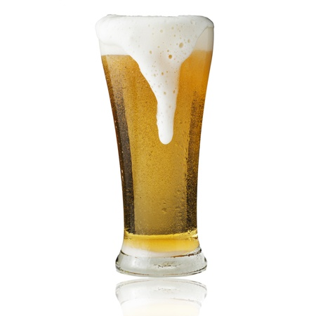 Fresh beer in glass with foam on yellow background photo