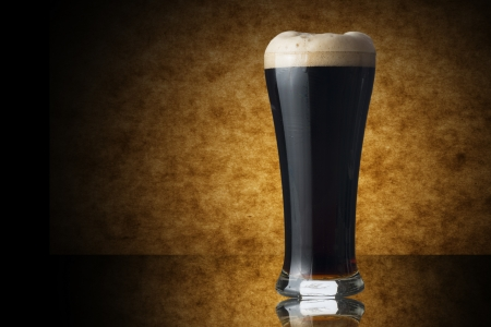 Glass of dark beer on yellow background photo