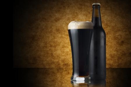 Glas dunkles Bier und eine Flasche auf gelbem Hintergrund