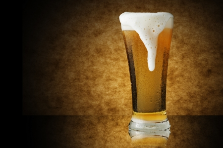 Cold glass of beer on yellow background photo