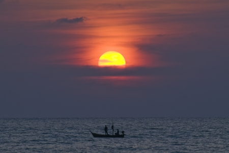 Fisherman on fishing boat at sunset photo