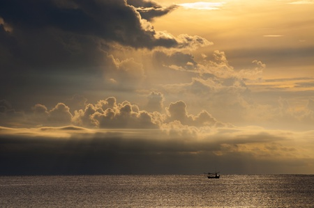 Fisherman in boat at sea with beatiful cloud in the sky photo