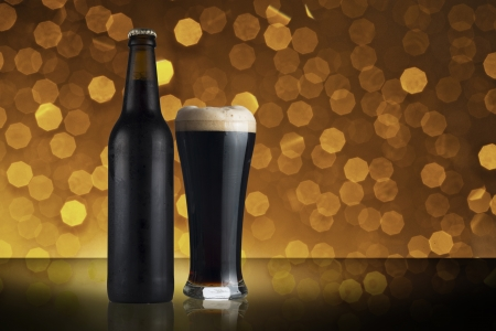 Bottle and glass of dark beer with beautiful bokeh background photo