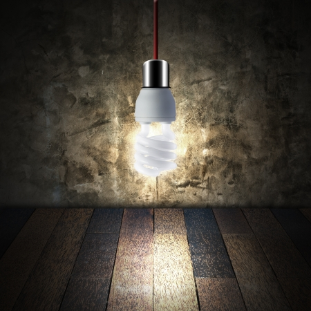 Light bulb in empty room with wooden floor and grunge wall   photo