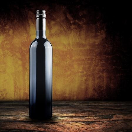 Wine bottle on wood with yellow grunge background photo