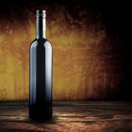 grunge bottle: Wine bottle on wood with yellow grunge background