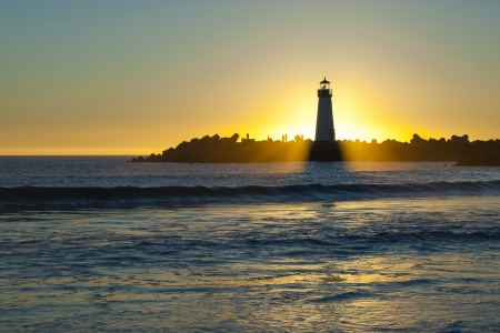 illuminative: Lighthouse with sunset in the background and ocean in the foreground Stock Photo