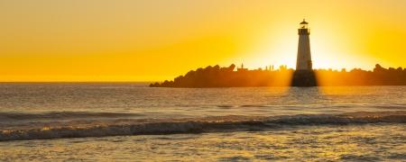 バック グラウンド、フォア グラウンドで海で夕日と灯台