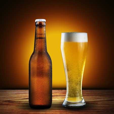 Bottle and glass of beer on wood table with yellow background photo