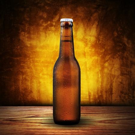 botella de licor: Botella de cerveza sobre la mesa de madera con fondo amarillo Foto de archivo
