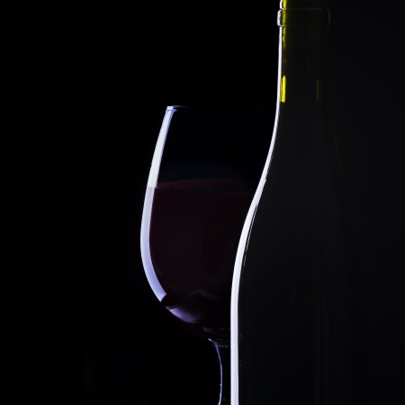 Glass and bottle of wine on black photo