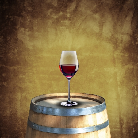 Glass of red wine on wood barrel with grunge background photo
