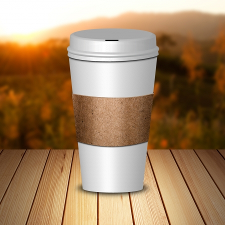 take away: Hot coffee in take away cup on wood and sunset sky