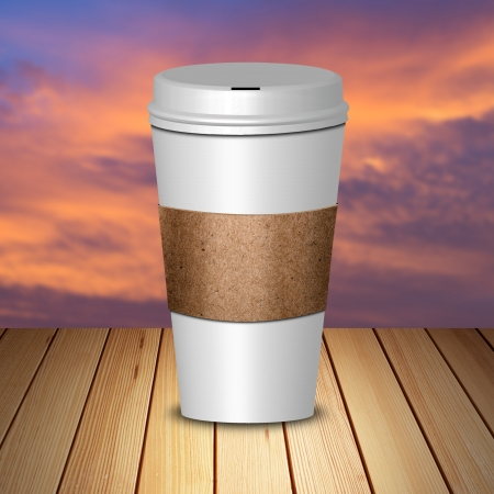 Hot coffee in take away cup on wood and sunset sky photo