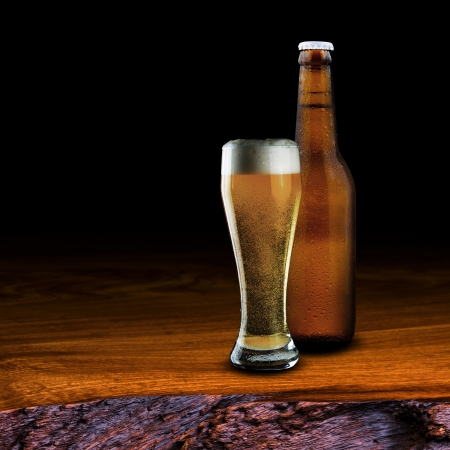 wino: Bottle and Glass of beer on wood table on black background Stock Photo