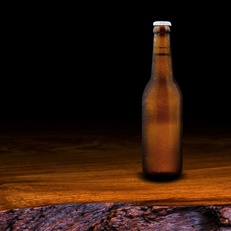 wino: Bottle of beer on wood table on black background Stock Photo