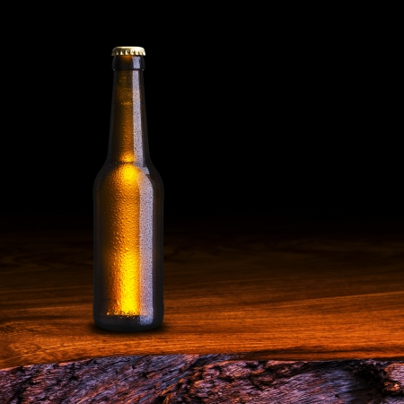 dewed: Cold Bottle of beer on wood table Stock Photo