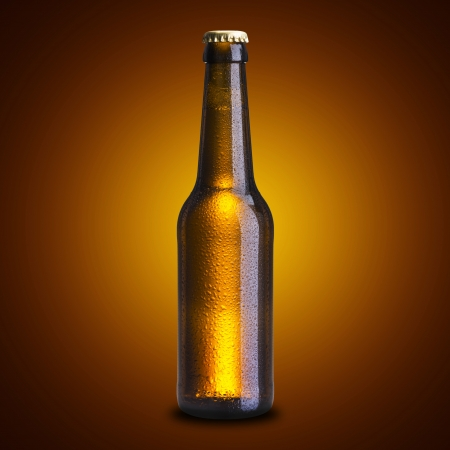 dewed: Cold beer bottle on yellow background