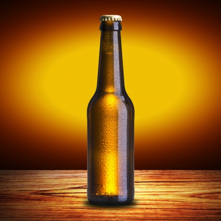 brown bottle: Cold Bottle of beer on wood table Stock Photo
