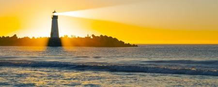 Faro con haz de luz en el océano